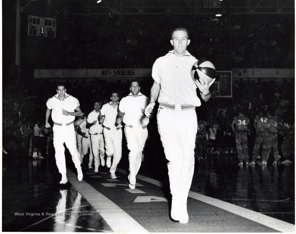 "[""Willie Akers leads the team down the carpet and Jerry West is on the left. The carpet is rolled out before each home game for the WVU team to enter on to the court. This is one of the best traditions in NCAA basketball. ""]"