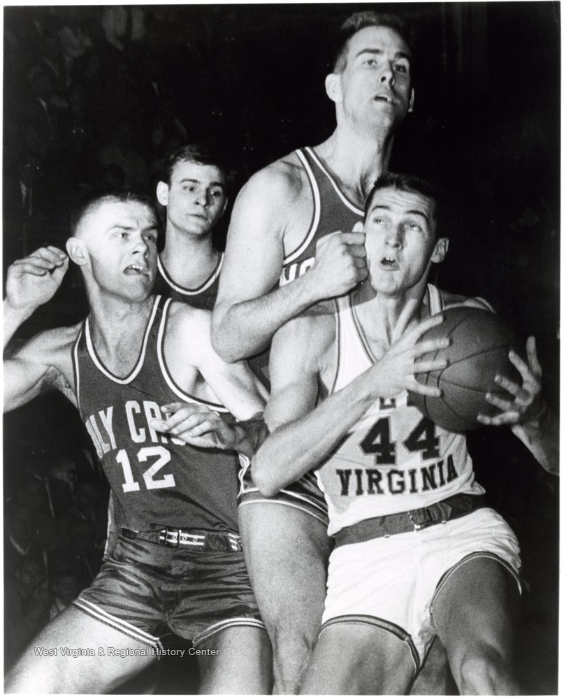 "[""Jerry West is fouled by Ralph Brandt in attempting a lay- up against Holy Cross. Number 12 is George Blaney.""]"
