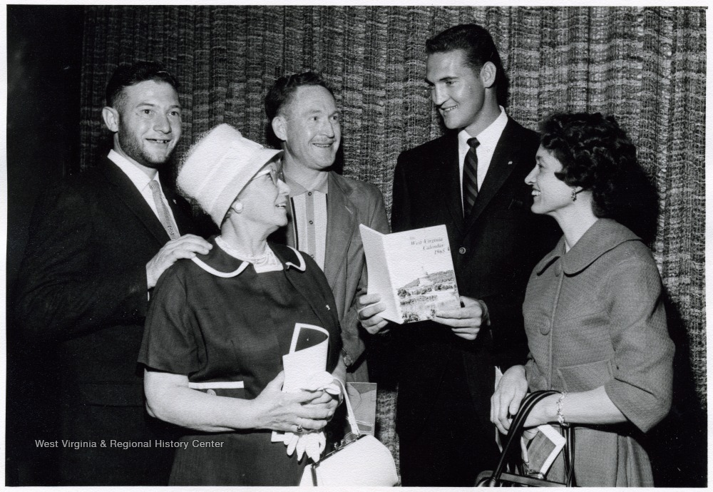 "[""A photograph of Jerry West (second from right) standing with Louise Larkey (right) and Victor Larkey (far left) of Weirton, W. Va., Mrs. O. J. White (front left) of Morgantown, W. Va., and Red Lyons (rear right) of Raleigh County, W. Va.""]"