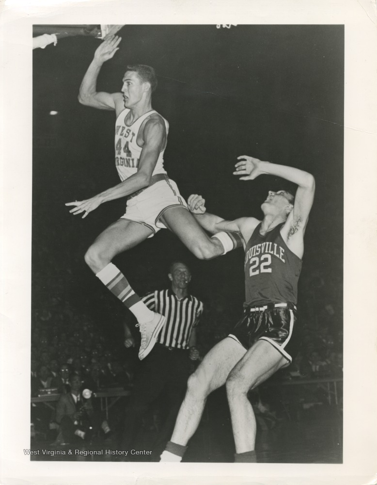 "[""West, left, flies past Louisville's John Turner during the 1959 NCAA Semi-Finals. The Mountaineers won this game 93-78, with 38 points scored by West alone. ""]"