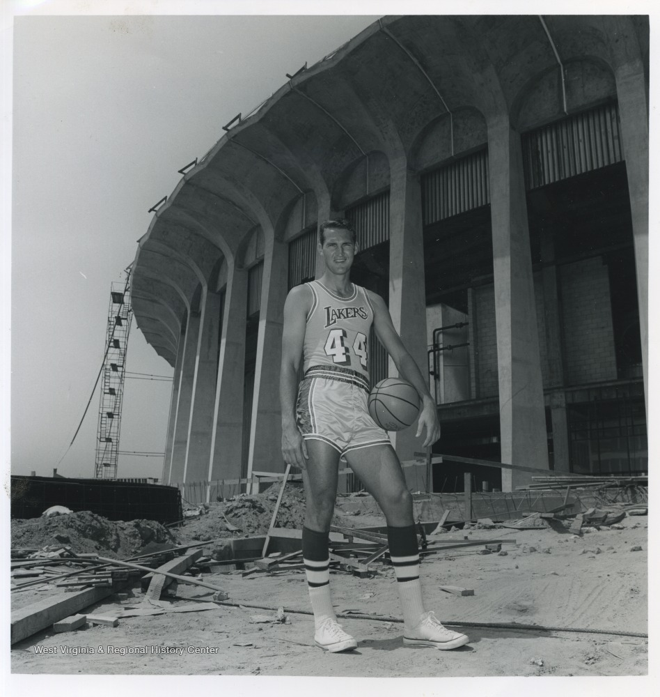 "[""West is pictured holding a basketball on the construction site of the L.A. Forum.  He played for the Lakers from 1960-1974.""]"