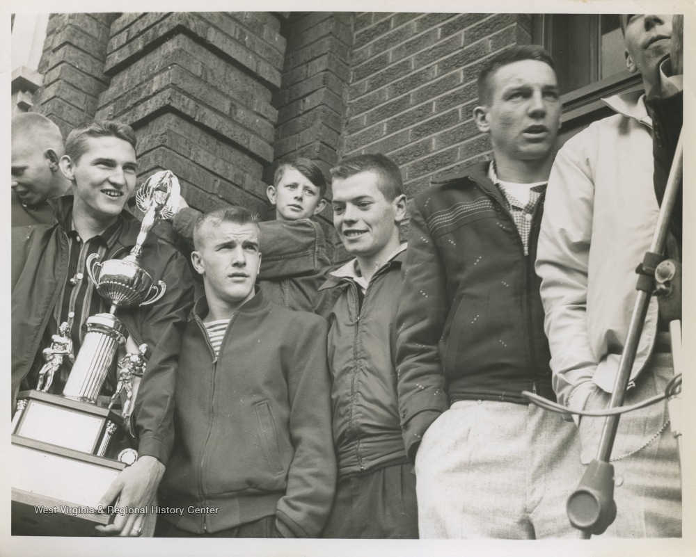 "[""Jerry West, pictured holding the trophy, is outside of East Bank High School after leading his team to championship victory. West was the team's starting small forward. He was named All-State from 1953–56, then All-American in 1956 when he was West Virginia Player of the Year, becoming the state's first high-school player to score more than 900 points in a season.""]"