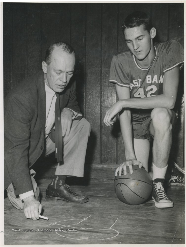 "[""West, right, is pictured with East Bank coach Roy Williams, who is stressing defense techniques. West was the team's starting small forward. He was named All-State from 1953–56, then All-American in 1956 when he was West Virginia Player of the Year, becoming the state's first high-school player to score more than 900 points in a season.""]"