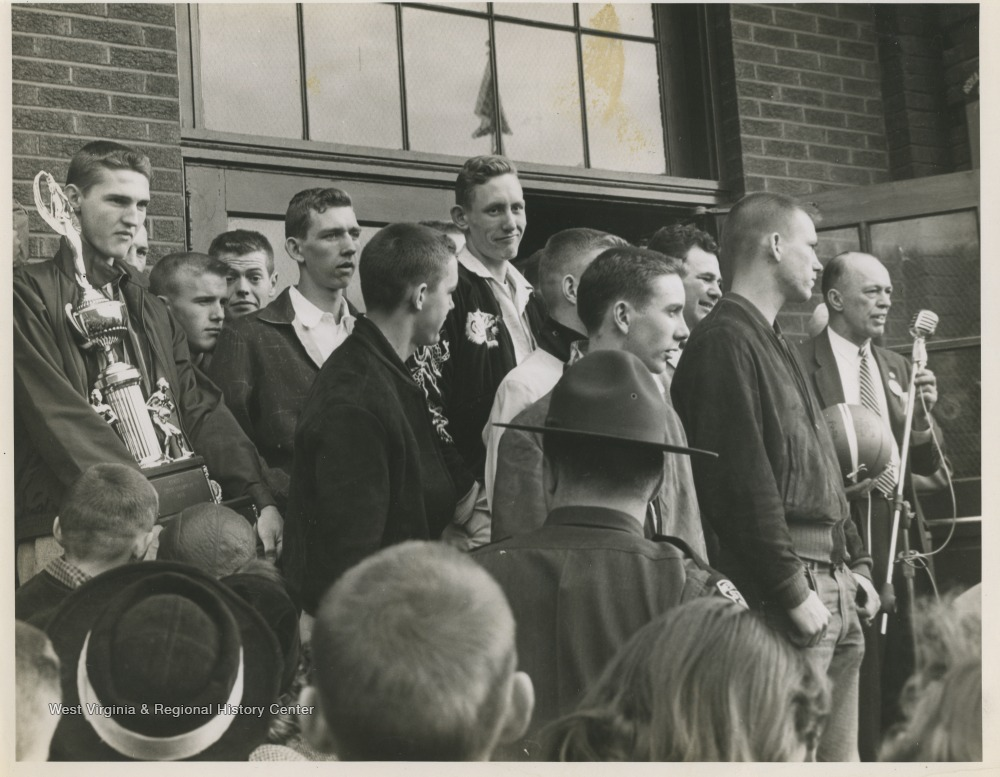 "[""Jerry West, pictured on the left holding a trophy, is outside of East Bank High School after leading his team to championship victory. West was the team's starting small forward. He was named All-State from 1953–56, then All-American in 1956 when he was West Virginia Player of the Year, becoming the state's first high-school player to score more than 900 points in a season.""]"