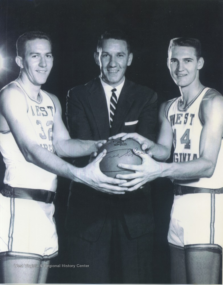 "[""West, right, poses with West Virginia University Basketball Coach Fred Schaus, center, and teammate Willie Akers, left, while holding a basketball. West played for West Virginia University before he was drafted by the Los Angeles Lakers. ""]"