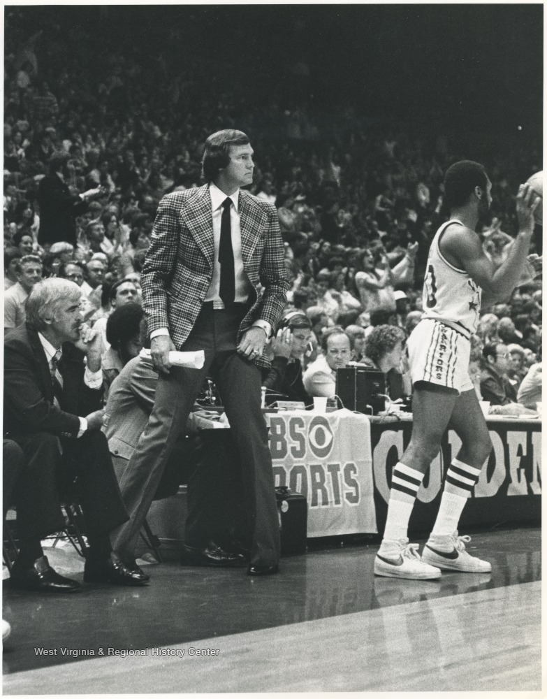 "[""West, wearing a patterned blazer, with Jack McCloskey, left, look out onto the court as the game progresses. After fourteen years of playing for the team, West rejoined the Lakers as coach for three seasons between 1976 and 1982. He led the team to the playoffs each season. ""]"
