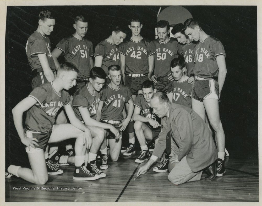 "[""Jerry West, No. 42, is pictured with his high school basketball team and Coach Roy Williams.West was the team's starting small forward. He was named All-State from 1953–56, then All-American in 1956 when he was West Virginia Player of the Year, becoming the state's first high-school player to score more than 900 points in a season.West also led his team to victory at the West Virginia State High School Basketball Championship in 1956, a first for the team. ""]"
