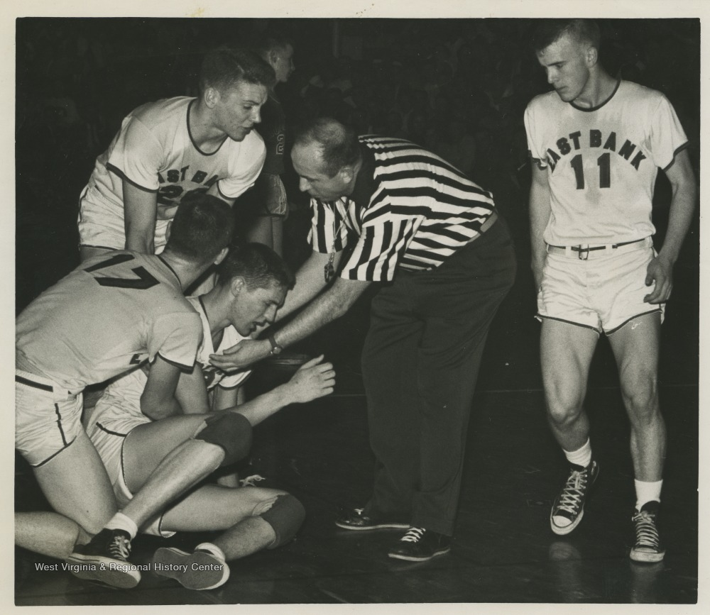 "[""A referee and teammates come to West's aid during a high school basketball game.West was the East Bank High School's starting small forward. He was named All-State from 1953–56, then All-American in 1956 when he was West Virginia Player of the Year, becoming the state's first high-school player to score more than 900 points in a season.The 1956 team secured the first ever state championship title for East Bank High School's basketball team. ""]"