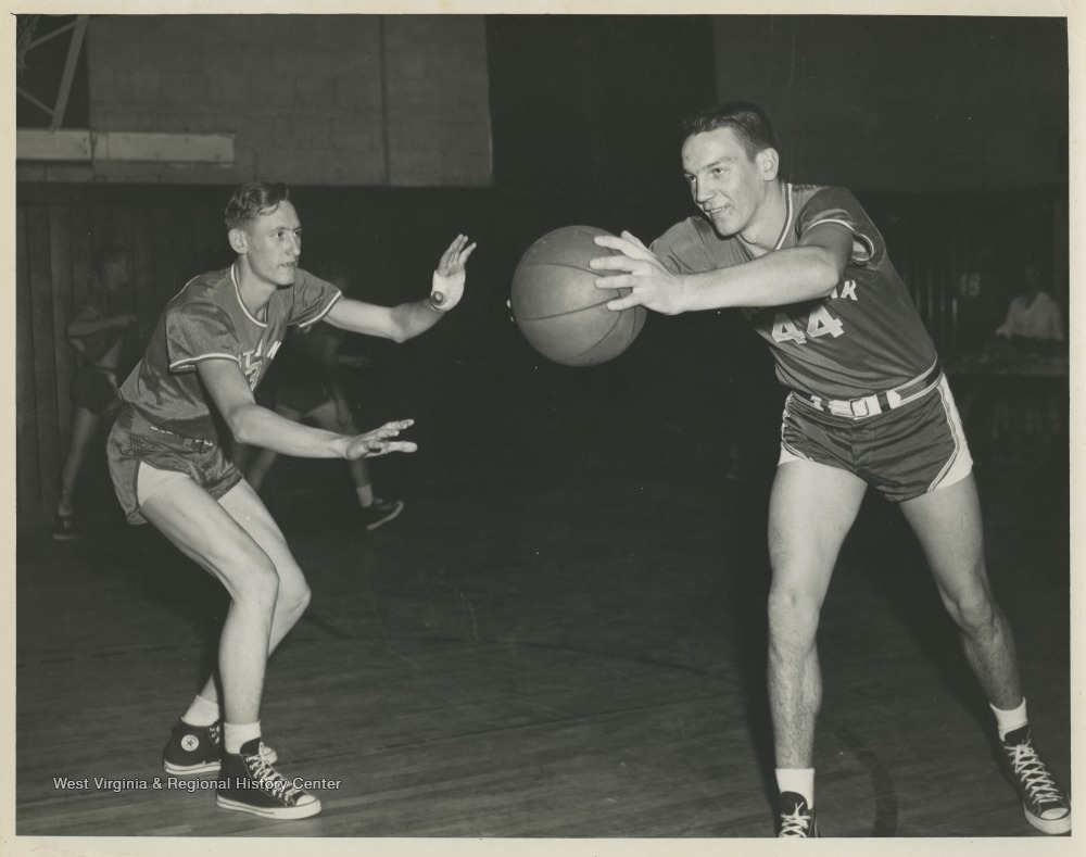 "[""Leonord Greer, left, and Robert Buckley, right, are pictured during a drill at practice. The boys were teammates of Jerry West during his high school basketball career.The 1956 basketball team secured the first ever state championship title for the high school.""]"