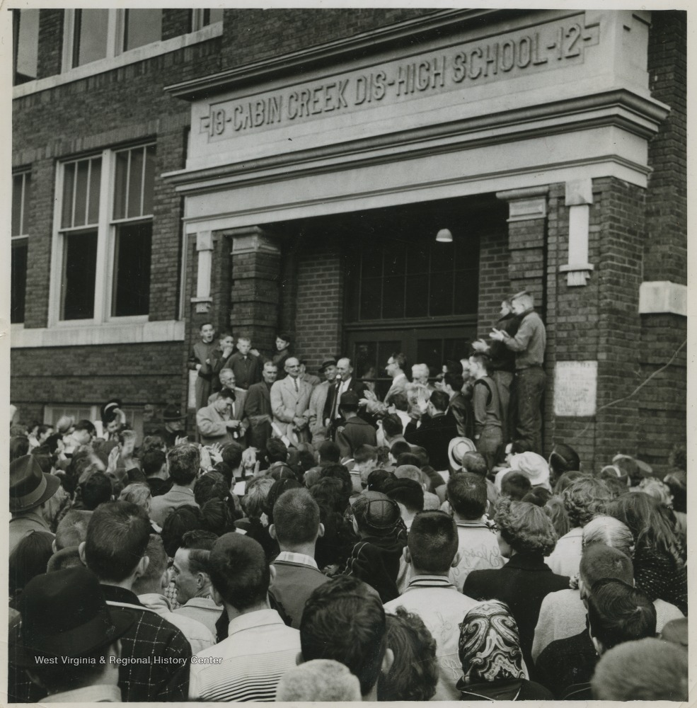 "[""Coach Roy E. Williams stands behind a microphone to address the crowd. Jerry West led the East Bank High School basketball team to secure its first ever state championship title.West was the team's small starting forward. He was named All-State from 1953–56, then All-American in 1956 when he was West Virginia Player of the Year, becoming the state's first high-school player to score more than 900 points in a season.""]"