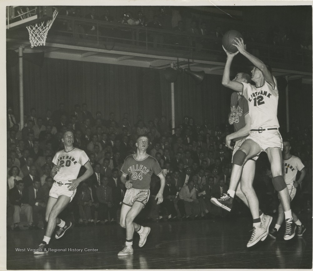 "[""With this shot, West (No. 12) makes the shot that scores him a new state high school record of 860 points in a season with only 6:50 left in the game. Also on the court is Bob Green (No. 20) of East Bank and Bob Short (No. 24) of Mullens.West was East Bank High School's small starting forward. He was named All-State from 1953–56, then All-American in 1956 when he was West Virginia Player of the Year, becoming the state's first high-school player to score more than 900 points in a season.In 1956, West led his team to secure its first ever state championship title. ""]"
