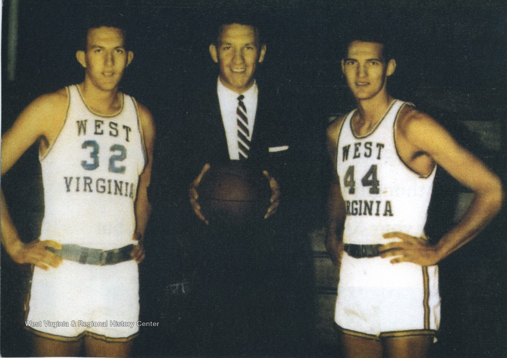 "[""West (No. 44) poses on the right with West Virginia University basketball coach Fred Schaus (center) and Willie Akers (left). ""]"