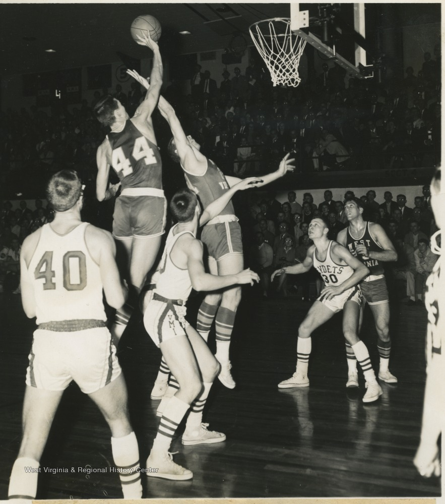 "[""West (No. 44) is pictured midair as he prepares to shoot two of his overall thirty-nine points at the game against VMI. The Mountaineers won with a 101-71 victory. ""]"