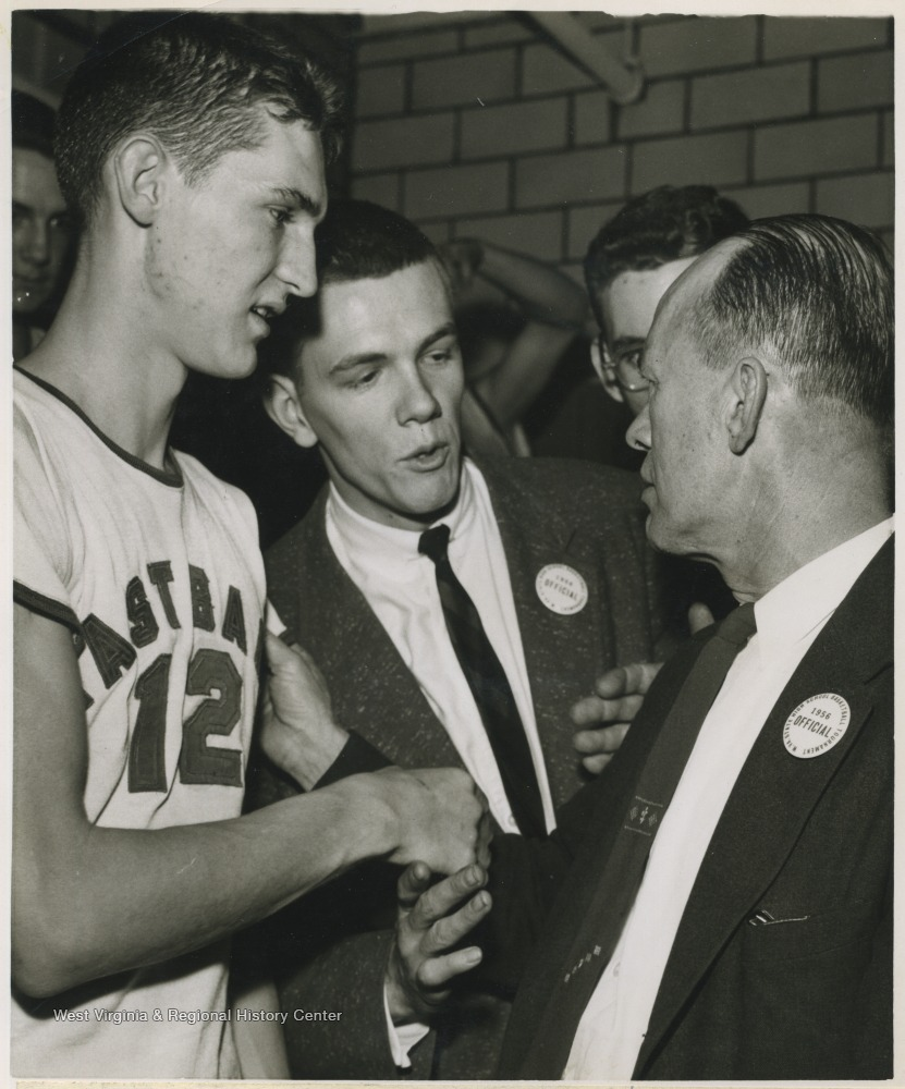 "[""East Bank High School basketball coach Roy E. Williams, right, shakes the hand of Jerry West, left, in the dressing room after beating Mullens High School in Morgantown and winning the state championship title.West was East Bank's starting small forward. He was named All-State from 1953–56, then All-American in 1956 when he was West Virginia Player of the Year, becoming the state's first high-school player to score more than 900 points in a season.""]"