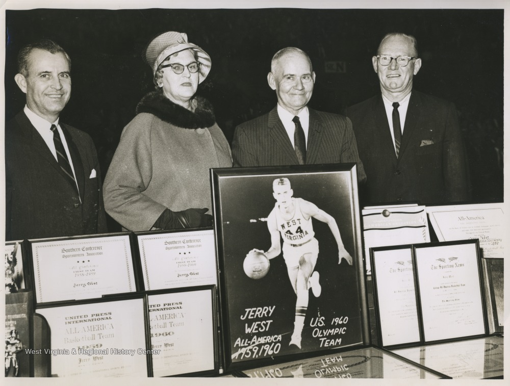 "[""Mr. and Mrs. West are pictured in the center in between two unidentified gentlemen. The four are standing behind a table covered by basketball star Jerry West's many awards during his college basketball career at West Virginia University. ""]"