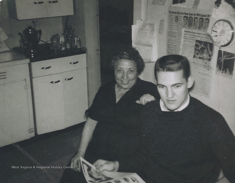 "[""Eulinda Dinardi, sister of Ann Dinardi and basketball star West are pictured in the Dinardi's kitchen reading a newspaper.West described Ann Dinardi as his \""mom away from home.\"" She had a special relationship with many of the basketball players because she lived steps away from the Old Field House.  Her home was on Beechurst Avenue. ""]"