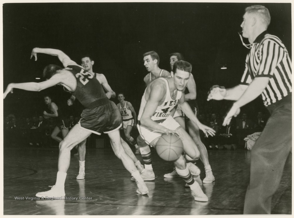 "[""Jerry West swept past Bev Vaughan (25) of William and Mary and scored a total of 38 points against William and Mary. WVU won 85-82 in the semi-finals of the 1959 Southern Conference Tournament.""]"