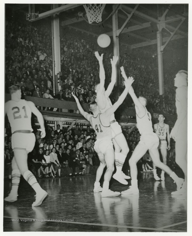 "[""West shoots the ball while opponents attempt to block him during a home WVU game""]"