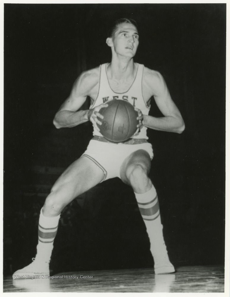 "[""Jerry West appears to be preparing to either make a basket or pass the ball to a teammate in this image.""]"