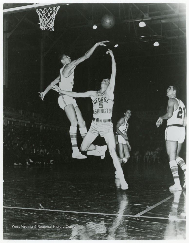 "[""West jumps to block GW's George Marshall and his layup shot during this 1958 game.  WVU won 93 to 66.""]"