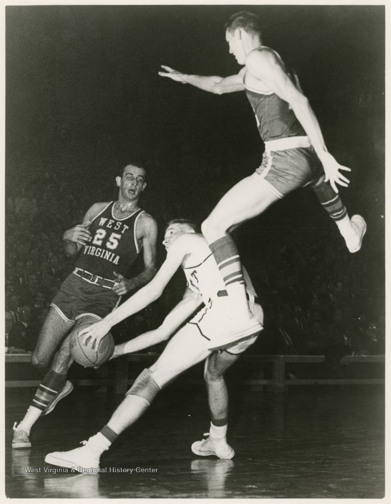 "[""West jumps to block Pitt's Dick Falenski as he attempts to shoot.  The Mountaineers won this game at Pittsburgh, 76-66.""]"