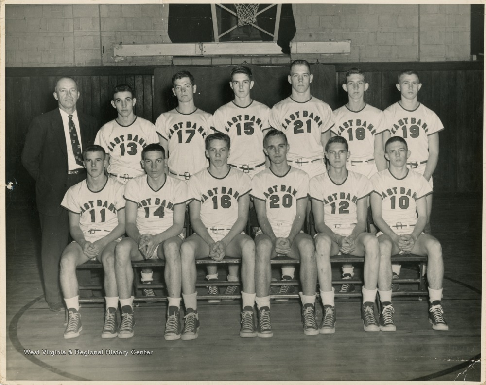 "[""Coach Roy Williams is in the back row.  Jerry West is wearing jersey number 12 and is  seated in the front row.""]"