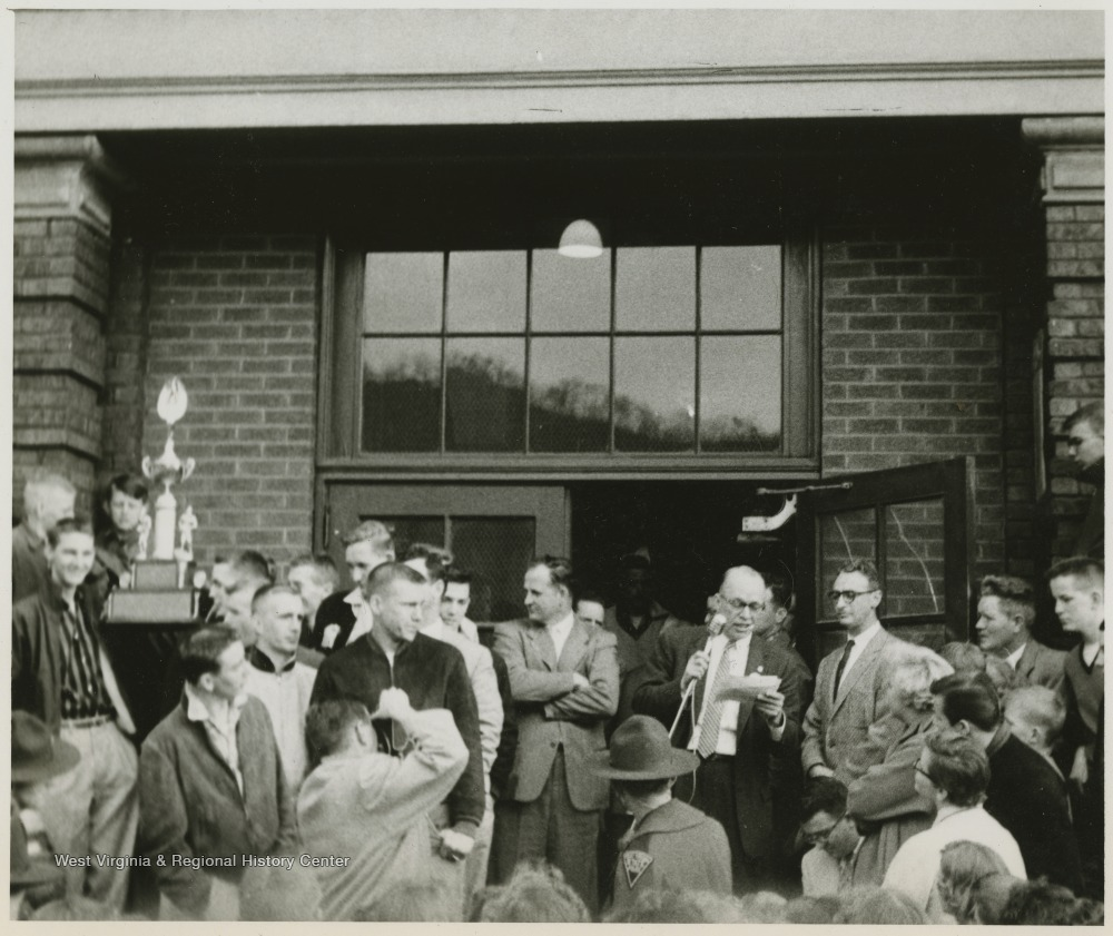 "[""A crowd celebrates the victory in front of the East Bank High School building. Jerry West is pictured in a striped shirt, standing beside a boy holding the trophy on the left of the photograph.West led the East Bank High School basketball team to its first ever West Virginia state championship title. He was named All-State from 1953–56, then All-American in 1956 when he was West Virginia Player of the Year, becoming the state's first high-school player to score more than 900 points in a season.West was born in Cheylan, W. Va. in 1938. After high school, he went on to play basketball for West Virginia University and then rose to fame as a player for the Los Angeles Lakers of the NBA before becoming a basketball coach and manager. ""]"