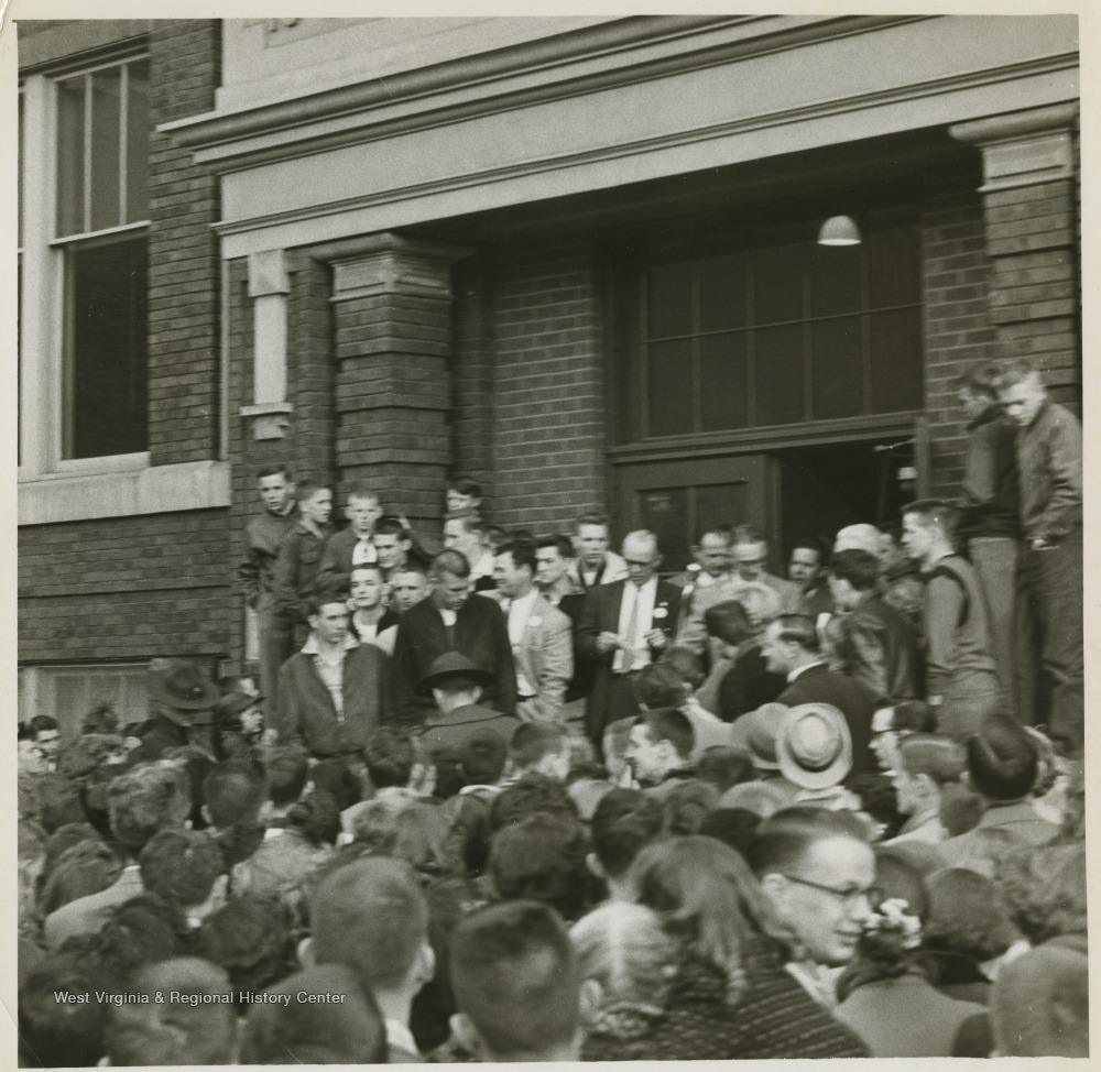 "[""A crowd celebrates the victory in front of East Bank High School.Jerry West led the East Bank High School basketball team to its first ever West Virginia state championship title. He was named All-State from 1953–56, then All-American in 1956 when he was West Virginia Player of the Year, becoming the state's first high-school player to score more than 900 points in a season.West was born in Cheylan, W. Va. in 1938. After high school, he went on to play basketball for West Virginia University and then rose to fame as a player for the Los Angeles Lakers of the NBA before becoming a basketball coach and manager. ""]"