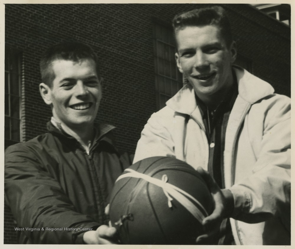 "[""Stover and Green pose with the game ball after securing the state championship victory.Jerry West led the East Bank High School basketball team to its first ever West Virginia state championship title. He was named All-State from 1953–56, then All-American in 1956 when he was West Virginia Player of the Year, becoming the state's first high-school player to score more than 900 points in a season.West was born in Cheylan, W. Va. in 1938. After high school, he went on to play basketball for West Virginia University and then rose to fame as a player for the Los Angeles Lakers of the NBA before becoming a basketball coach and manager. ""]"
