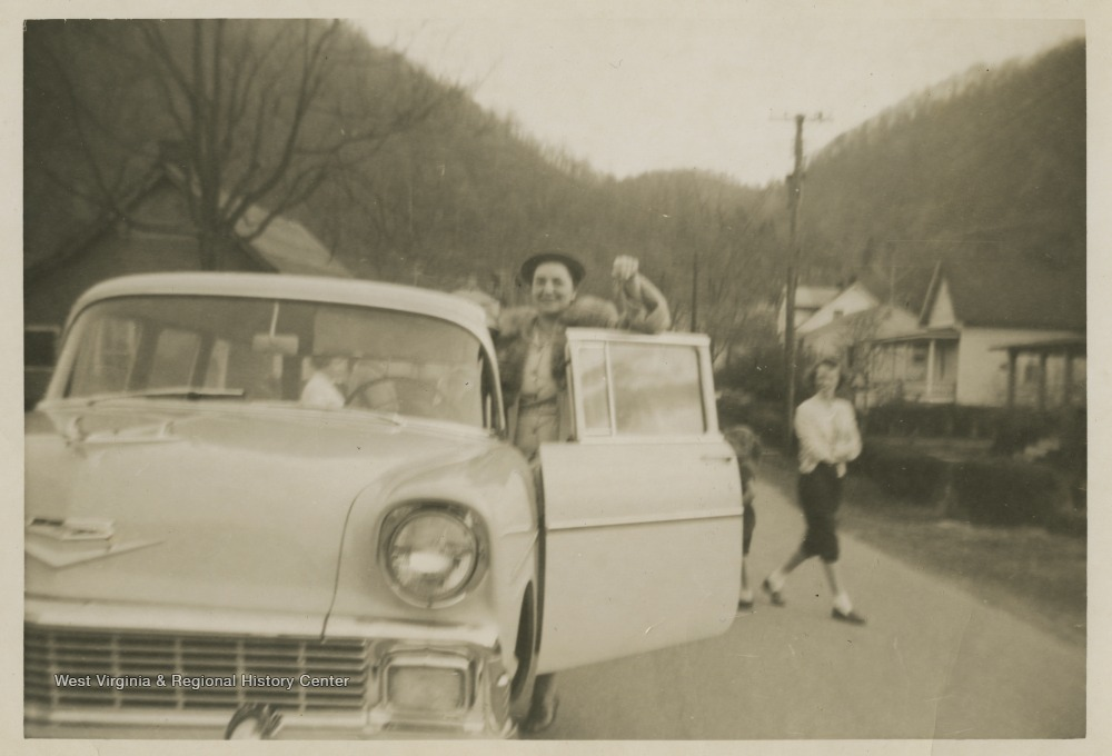 "[""Williams holds up the keys to a brand new Chevy station-wagon, which was bought for basketball coach Roy Williams and his family by the East Bank High School fans.Jerry West led the East Bank High School basketball team to its first ever West Virginia state championship title in 1956. ""]"