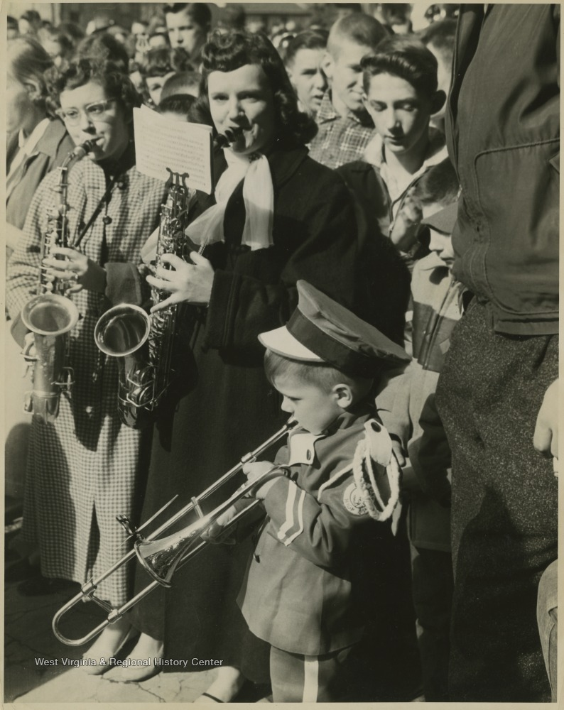 "[""Band members play to celebrate the East Bank High School basketball team winning its first ever state championship title. Young Clinton Jeffreys, mascot for the East Bank High School band, blows a horn to celebrate the homecoming of the State Basktball Champions.""]"