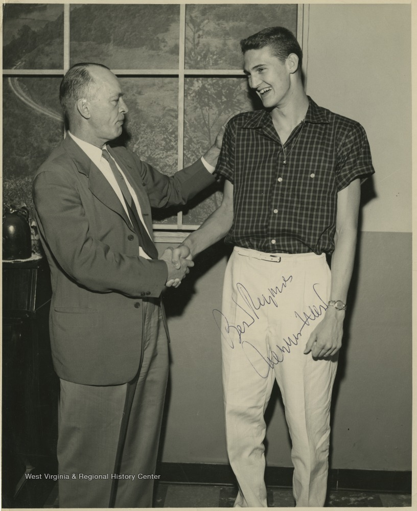 "[""Jerry West, right, shakes hands with Coach Williams, left.West led the East Bank High School basketball team to its first ever state championship victory as its starting small forward. He was named All-State from 1953–56, then All-American in 1956 when he was West Virginia Player of the Year, becoming the state's first high-school player to score more than 900 points in a season.West was born in Cheylan, W. Va. in 1938. After high school, he went on to play basketball for West Virginia University and then rose to fame as a player for the Los Angeles Lakers of the NBA before becoming a basketball coach and manager. ""]"