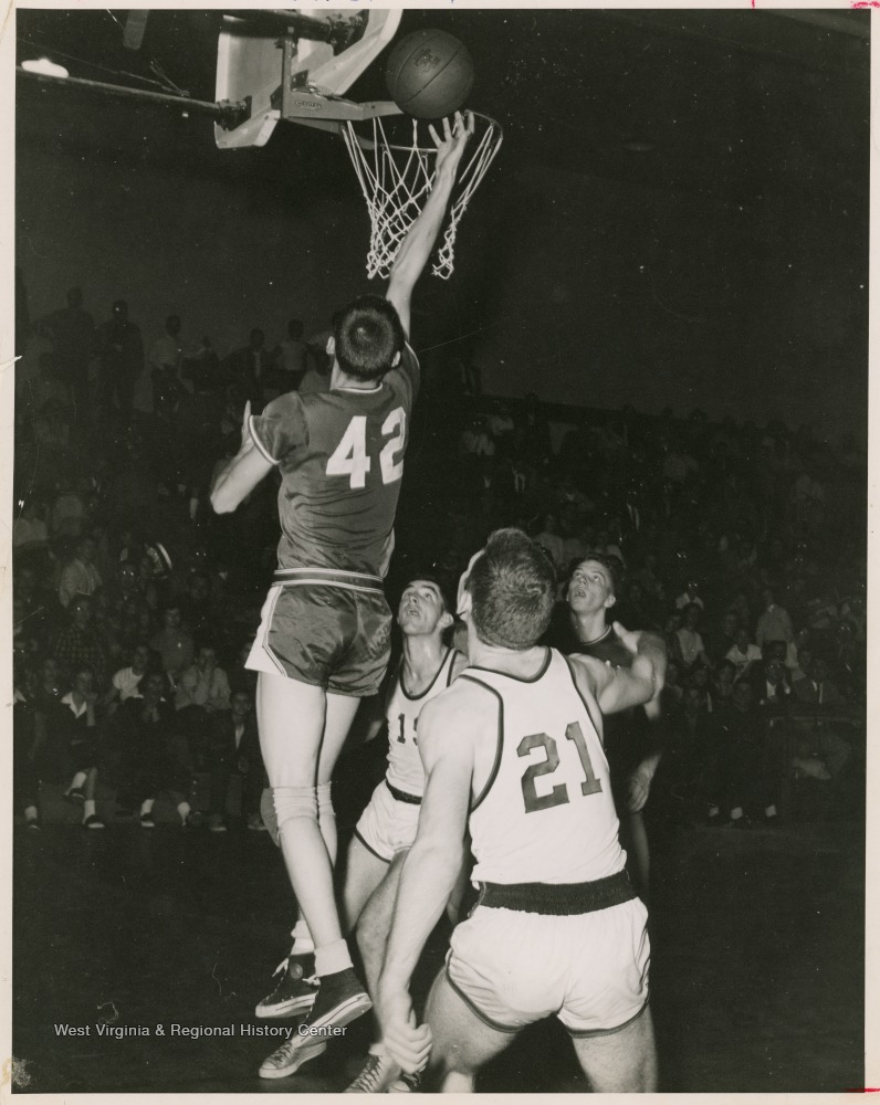 "[""Jerry West led the East Bank High School basketball team to its first ever state championship victory as its starting small forward. He was named All-State from 1953–56, then All-American in 1956 when he was West Virginia Player of the Year, becoming the state's first high-school player to score more than 900 points in a season.West was born in Cheylan, W. Va. in 1938. After high school, he went on to play basketball for West Virginia University and then rose to fame as a player for the Los Angeles Lakers of the NBA before becoming a basketball coach and manager. ""]"