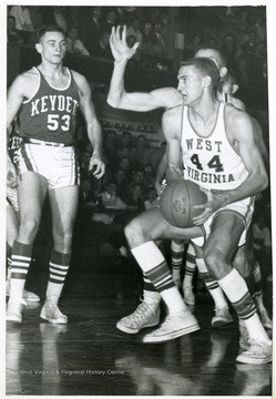 'West Virginia's Mr. Everything, Jerry West (44) slips by a Virginia Military (Institute) defender on his way to scoring one of the 12 field goals he scored 12/14. West was outscored by VMI's Joe Gedro (53) who tallied 30. WVU won, 91-76. UPI Telephoto.'