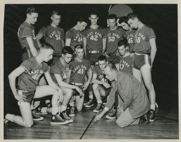 Jerry West, No. 42, is pictured with his high school basketball team and Coach Roy Williams.West was the team's starting small forward. He was named All-State from 1953–56, then All-American in 1956 when he was West Virginia Player of the Year, becoming the state's first high-school player to score more than 900 points in a season.West also led his team to victory at the West Virginia State High School Basketball Championship in 1956, a first for the team.