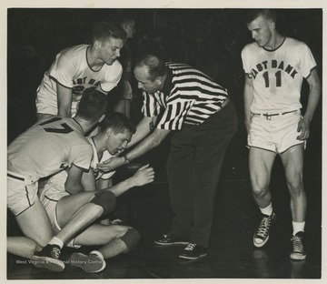 A referee and teammates come to West's aid during a high school basketball game.West was the East Bank High School's starting small forward. He was named All-State from 1953–56, then All-American in 1956 when he was West Virginia Player of the Year, becoming the state's first high-school player to score more than 900 points in a season.The 1956 team secured the first ever state championship title for East Bank High School's basketball team.