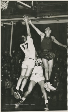 East Bank High School's Gary Stover, No. 17, and Morgantown's Jay Jacobs, No. 3, jump for a rebound during the championship game. Jerry West, not pictured, was also playing at this game as the team's starting small forward.West led East Bank High School to victory at this game, scoring 43 of the 71 points against Morgantown. The final score was 71-56. It was the first time East Bank High School won the state championship title.