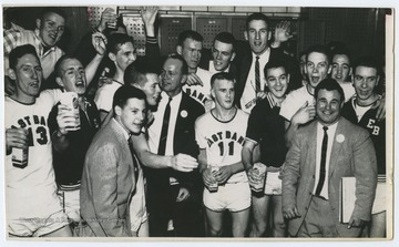Jerry West and teammates are pictured celebrating and drinking milk in a locker room with their coaches. The 1956 team secured the first ever state championship title for East Bank High School's basketball team.West was the team's starting small forward. He was named All-State from 1953–56, then All-American in 1956 when he was West Virginia Player of the Year, becoming the state's first high-school player to score more than 900 points in a season.