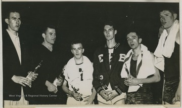 Pictured from left to right is Willie Akers of Mullens High School, Mr. Hurt from Beckley High School, Jack Landers from East Bank High School, Jerry West from East Bank High School, Jay Jacobs from Morgantown High School, and Mr. Davis from Morgantown High School.West was East Bank High School's starting small forward. He was named All-State from 1953–56, then All-American in 1956 when he was West Virginia Player of the Year, becoming the state's first high-school player to score more than 900 points in a season.He team secured the first ever state championship title for East Bank High School's basketball team.