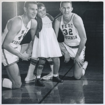 West, left, and Akers, right, pose with an unidentified young girl.