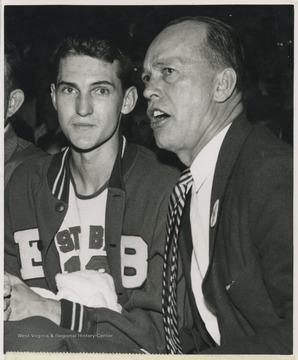 Williams, right, seems to be telling his star, Jerry West, left, not to worry after West fouled out of the game with 5:27 minutes left to play.West lead East Bank High School to secure its first ever state championship title as the team's starting small forward. He was named All-State from 1953–56, then All-American in 1956 when he was West Virginia Player of the Year, becoming the state's first high-school player to score more than 900 points in a season.