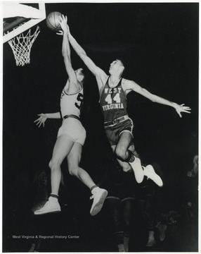 "West, the ""tallest player in basketball"" at 6'3"" keeps Smith from successfully making a shot. At this game, West Virginia University handed Kentucky their fifth home defeat in 15 years.Both West and Smith made the United States Olympic team two years later in 1960."