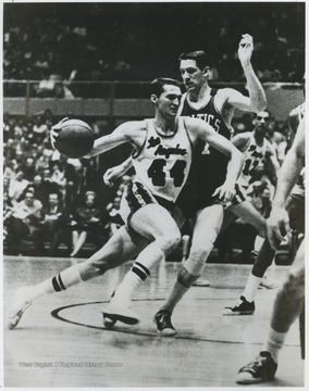 West (No.44), a twelve-time all-star by the time of this photograph, accelerates past Celtics player John Havlicek.