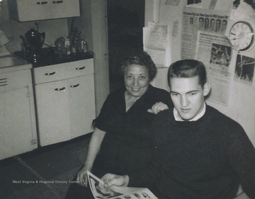 "Eulinda Dinardi, sister of Ann Dinardi and basketball star West are pictured in the Dinardi's kitchen reading a newspaper.West described Ann Dinardi as his ""mom away from home."" She had a special relationship with many of the basketball players because she lived steps away from the Old Field House.  Her home was on Beechurst Avenue."