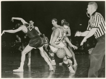 Jerry West swept past Bev Vaughan (25) of William and Mary and scored a total of 38 points against William and Mary. WVU won 85-82 in the semi-finals of the 1959 Southern Conference Tournament.