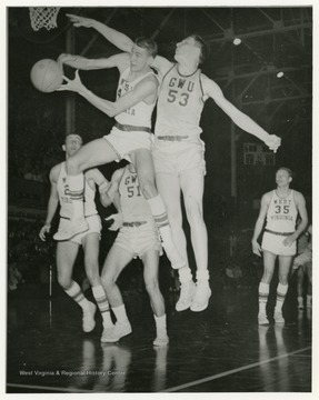 Jerry West and an opponent from GWU both jump toward the basket
