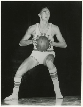 Jerry West appears to be preparing to either make a basket or pass the ball to a teammate in this image.