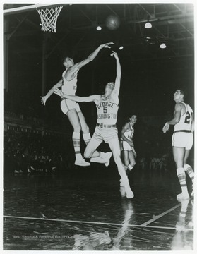 West jumps to block GW's George Marshall and his layup shot during this 1958 game.  WVU won 93 to 66.