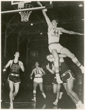 West scores against Canisius's Greg Britz with a back-handed field goal. WVU won the pictured game, 86 - 66.