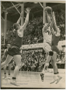 West shoots a layup in front of a large auditorium of spectators.  West was named All-State from 1953 to 1956 in high school.  He led East Bank High School to the state championship in 1956.